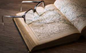 A set of glasses sitting on top of a 19th-century book of maps