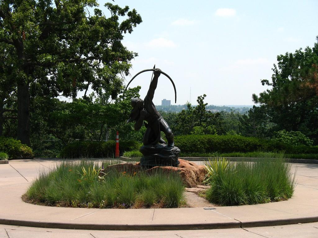Photograph of the sculpture of a Native American man shooting a bow that stands in front of the Gilcrease Museum in Tulsa, OK